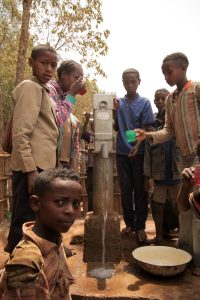 Children in Ethiopia pump water from a well