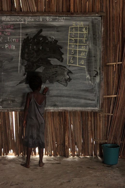 A child writes on a chalkboard in Madagascar