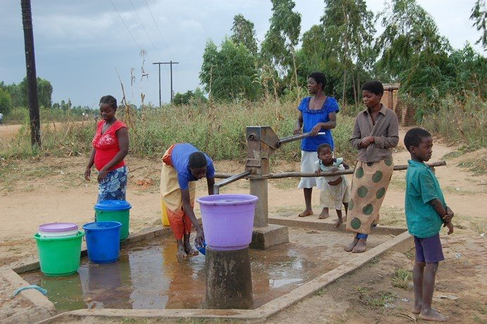 Mothers and children gathering water at a communal water pump