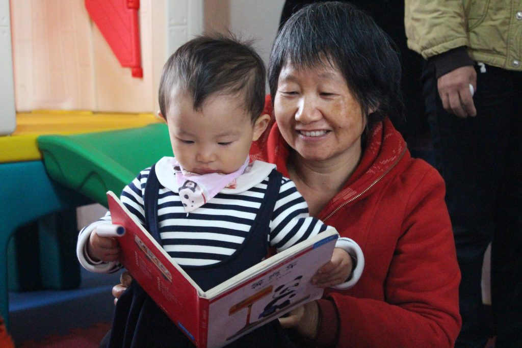 Child and caregiver at Ai Jia Village ECD