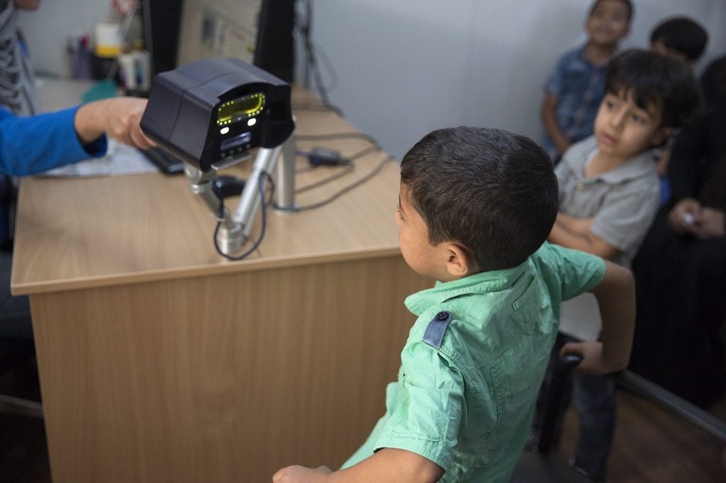 This child is having his ocular identity taken in Amman registration centre. It is sometimes a challenge. Picture by Ann Luyckx.