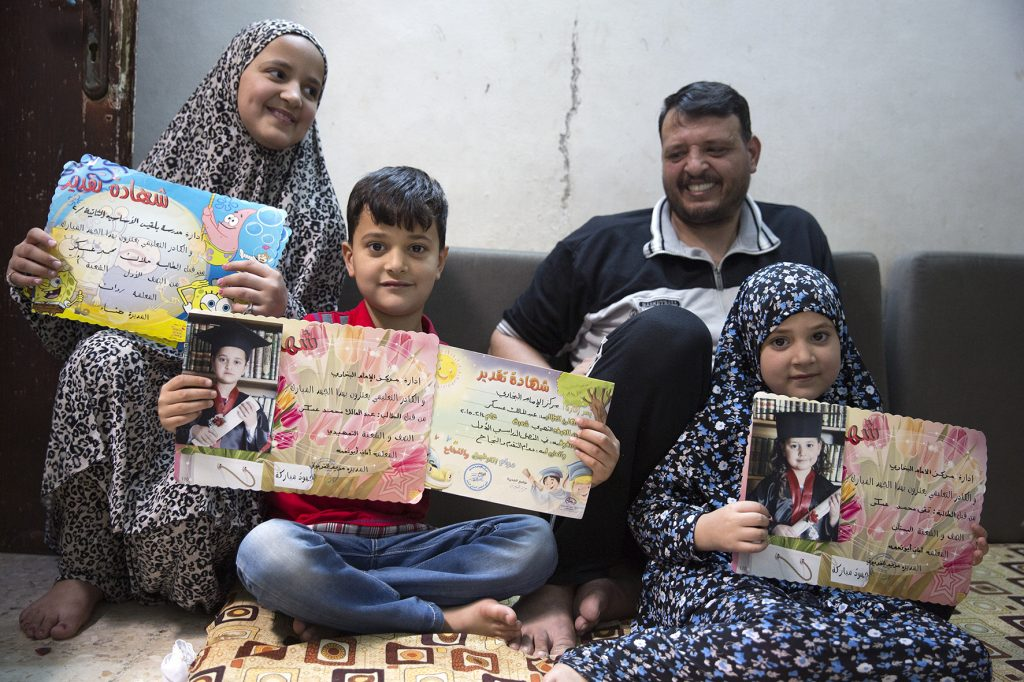 Malak, Abdul and Tuqa show us their school reports. Their father, Mohammed, is looking proud.