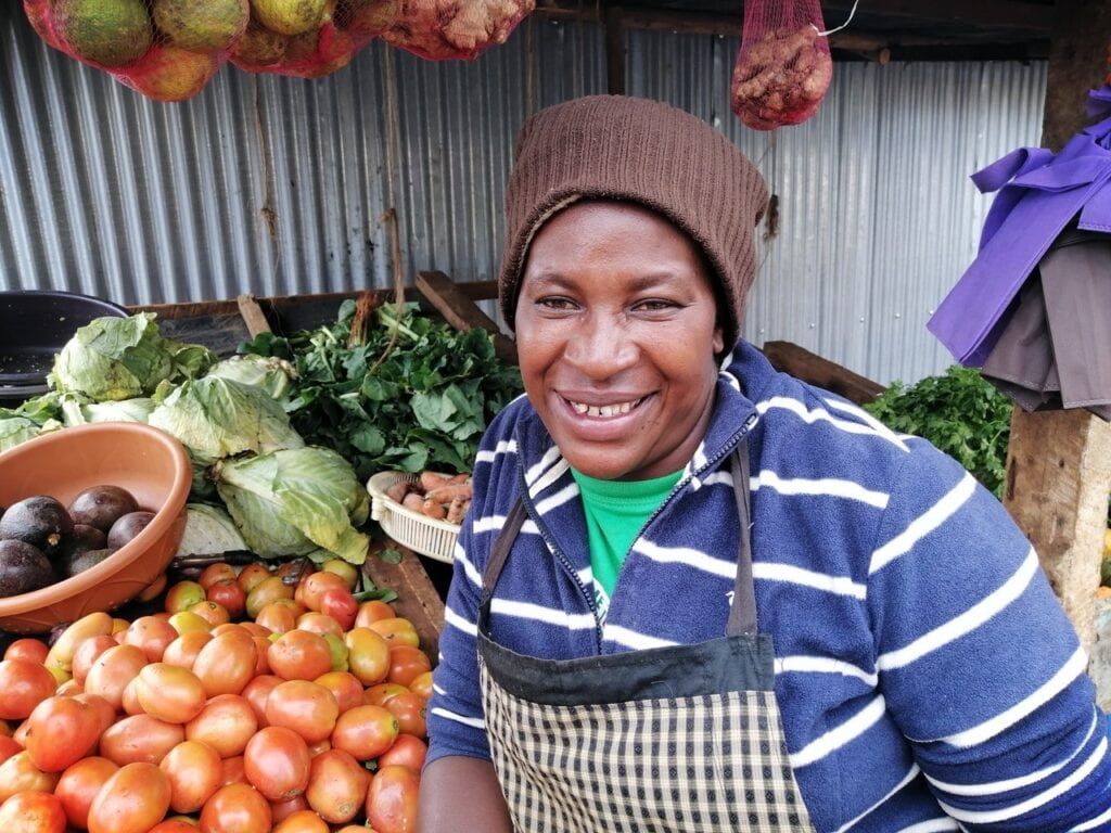 Female vegetable seller proudly displays her fresh produce.
